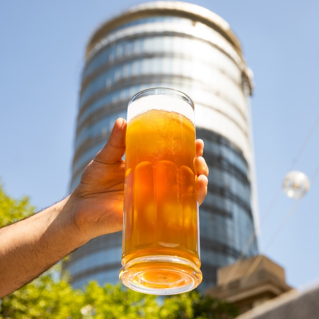 ビールのジョッキ、建物の背景を持つガラスを抱きかかえた Premium写真