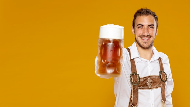 Pinta della birra della tenuta dell'uomo con lo spazio della copia Foto Gratuite