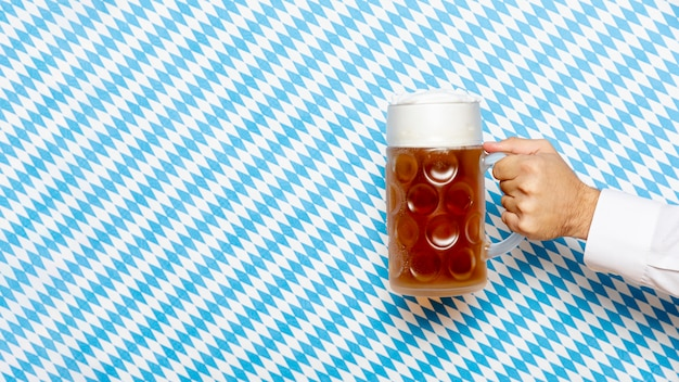 Man holding beer pint with patterned background Free Photo