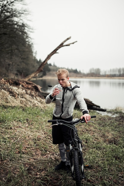 Man holding bicycle drinking water from bottle Free Photo