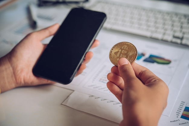 Man holding bitcoin and background with smartphone Premium Photo