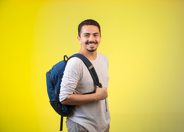 Man holding a blue backpack and smiling. Free Photo