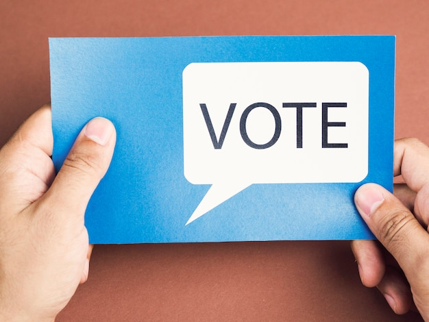 Man holding a blue card with a voting speech balloon Free Photo