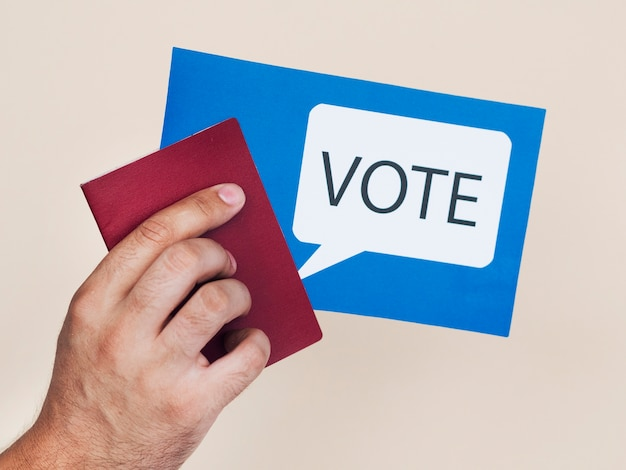 Man holding a blue card with voting speech bubble Free Photo