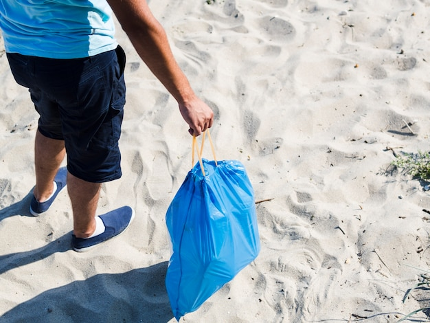 Man holding blue plastic bag of garbage at beach Free Photo