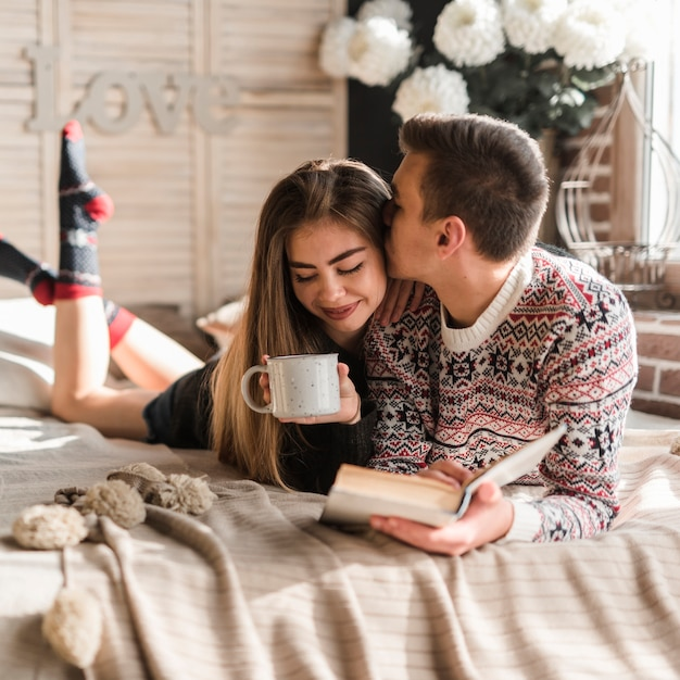 Man holding book in hand kissing her girlfriend holding cup of coffee lying on bed Free Photo