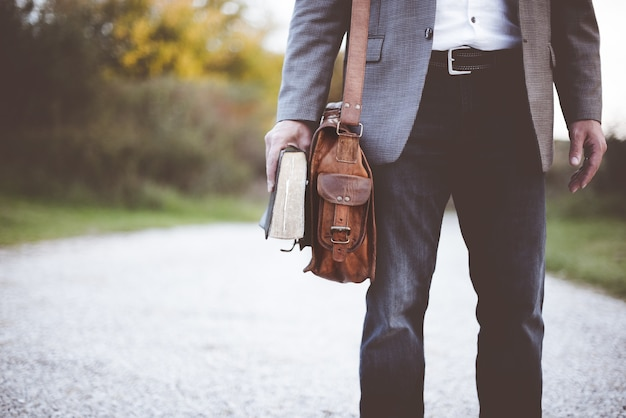 Человек, держащий книгу на дороге в дневное время Бесплатные Фотографии