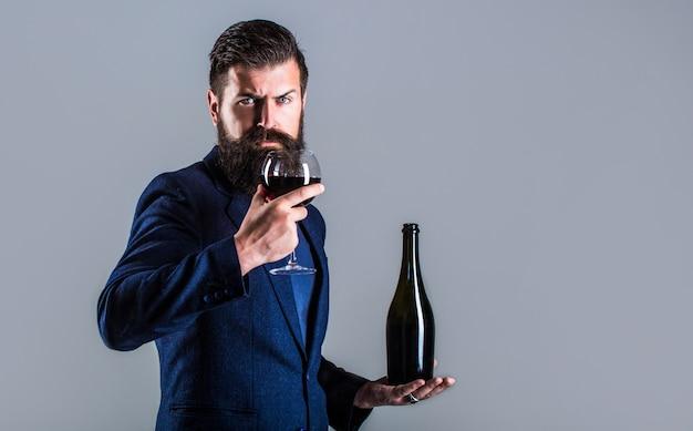 Мужчина держит бутылку с шампанским, вином. бутылка, бокал для красного вина. Premium Фотографии