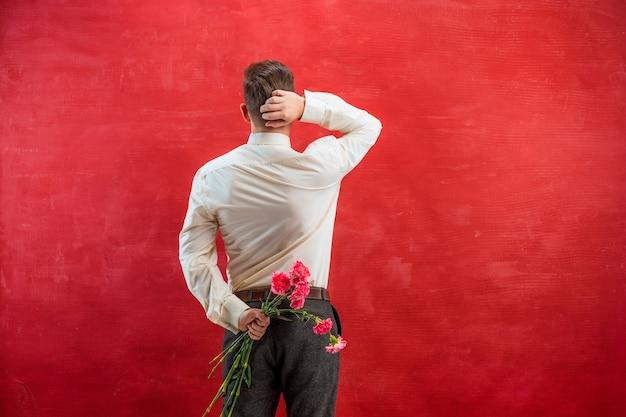 Мужчина держит букет гвоздик за спиной на фоне красной студии Бесплатные Фотографии