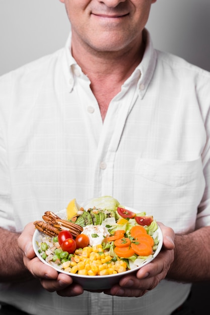 Man holding bowl of healthy food Free Photo