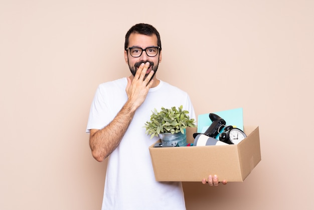 Man holding a box and moving in new home over isolated  with glasses and surprised Premium Photo