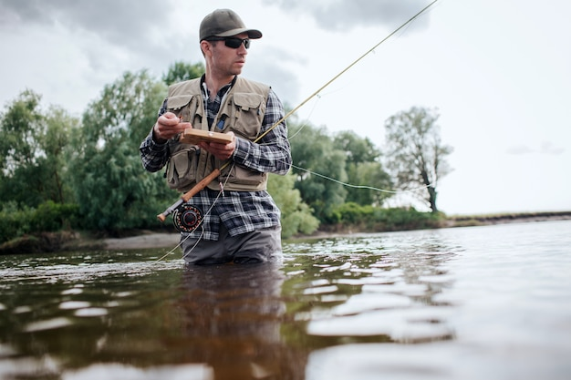Man holding box with flies and plastic artificial baits. he is holding one of them in hand. also guy has a fly rod. he is holding it with another hand. man looks straigght forward. Premium Photo