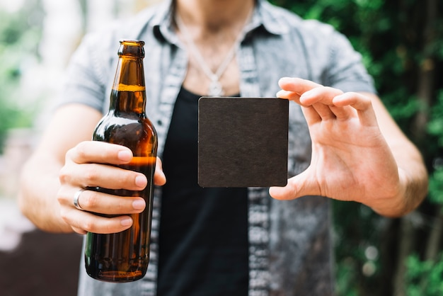 Man holding brown beer bottle and black blank card in hands Free Photo