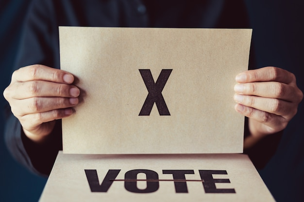 Man holding brown paper with x mark above vote box Premium Photo