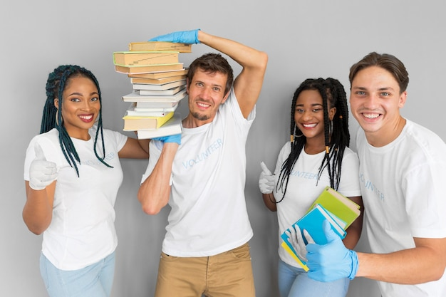 Uomo che tiene un mucchio di libri sulle spalle accanto ai suoi compagni Foto Gratuite