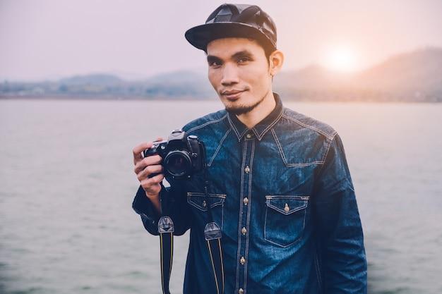 Man holding camera on hand at river vintage Premium Photo