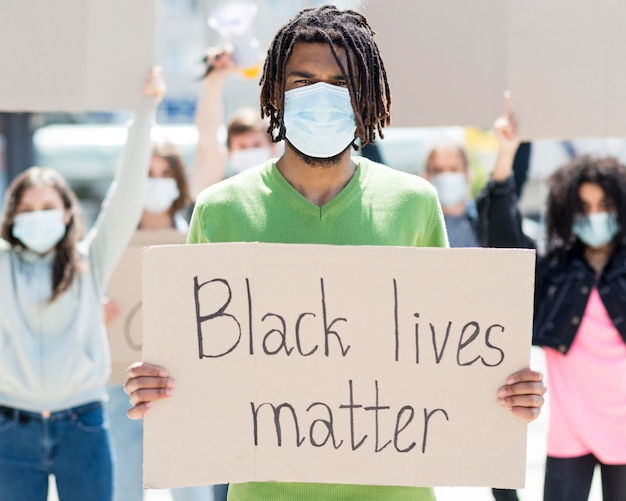 Man holding a cardboard with black lives matter quote Premium Photo