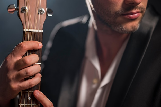 Man holding a chord on guitar close-up Free Photo