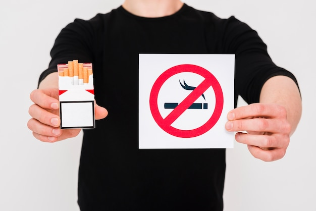 Man holding cigarettes packet and no smoking sign over white background Free Photo
