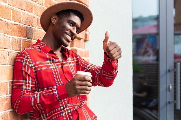 Uomo che tiene un caffè e che fa il pollice in alto gesto Foto Gratuite
