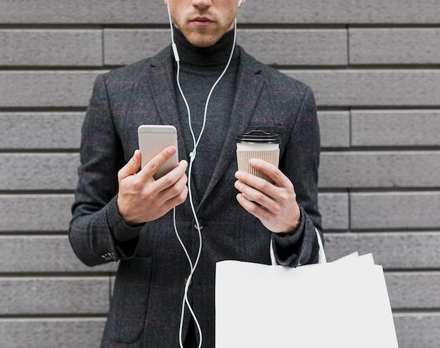 Man holding coffee and smartphone in his hands Free Photo