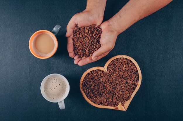블랙에 심장 모양의 그릇에 원두 커피와 커피를 들고 남자 무료 사진