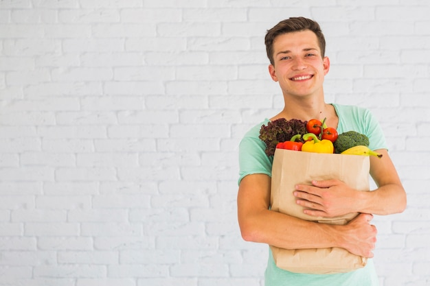 Man holding colorful fresh vegetables in grocery paper bag Free Photo