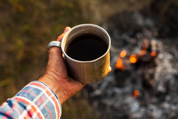 Man holding cup of coffee prepared outdoor Free Photo