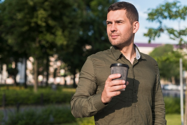 Man holding disposable coffee cup looking away at park Free Photo