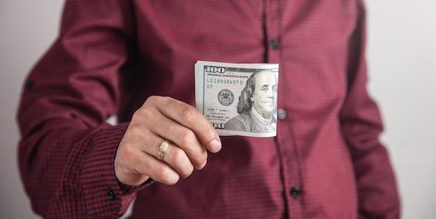 Мужчина держит доллары, стоя на сером фоне. Premium Фотографии