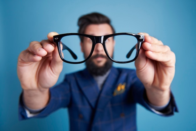 Man holding eyeglasses in front his face Free Photo