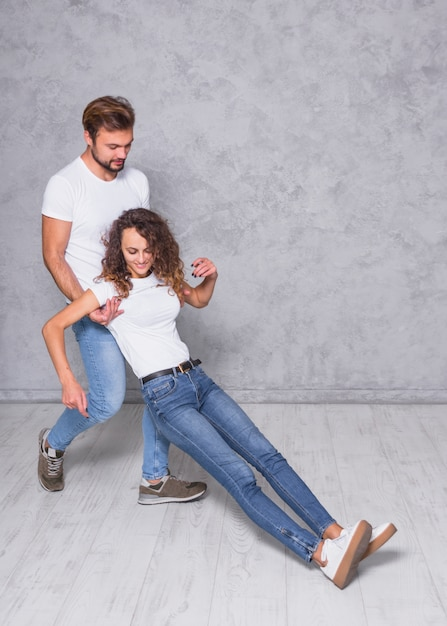 Man holding falling woman from behind Free Photo