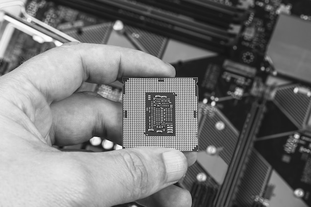Man holding fingers desktop processor 8th gen on background motherboard closeup top view, black and white photo Premium Photo