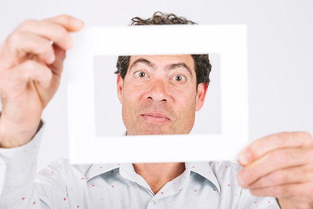 Man holding frame in front of his face Photo | Free Download