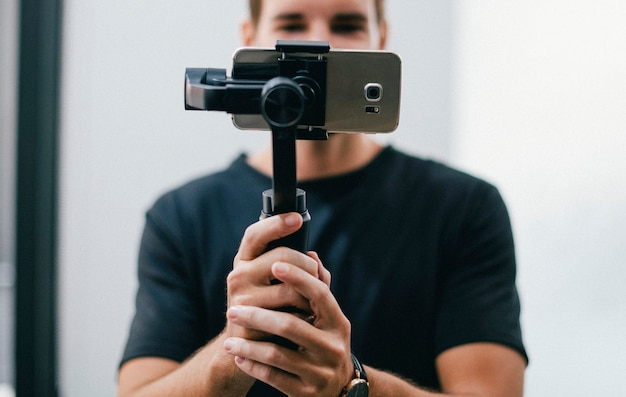 Man holding a gimbal with a phone Premium Photo