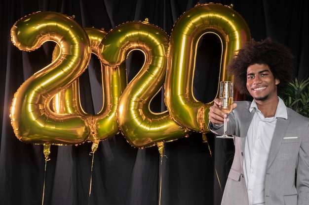 Man holding a glass of champagne and happy new year 2020 balloons Free Photo
