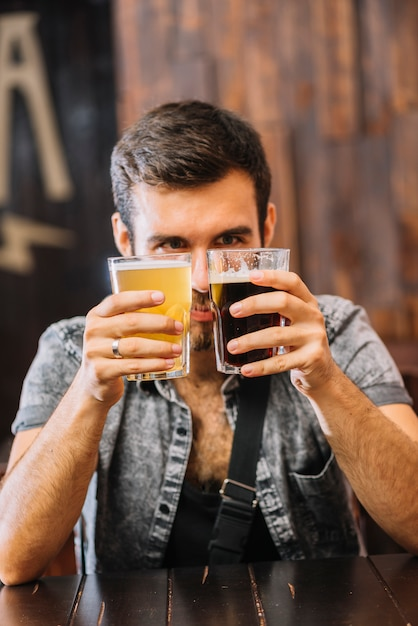 Man holding glasses of beer and rum in bar Free Photo