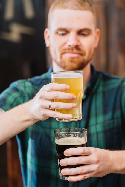 Man holding glasses of rum and beer Free Photo
