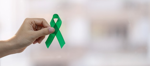 Man holding green ribbon for supporting people living and illness. liver, gallbladders bile duct, kidney cancer and lymphoma awareness month concept Premium Photo