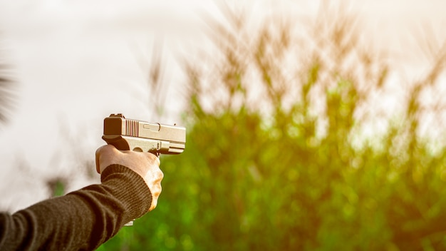A man holding a gun in hand. - violence and crime concept. Premium Photo