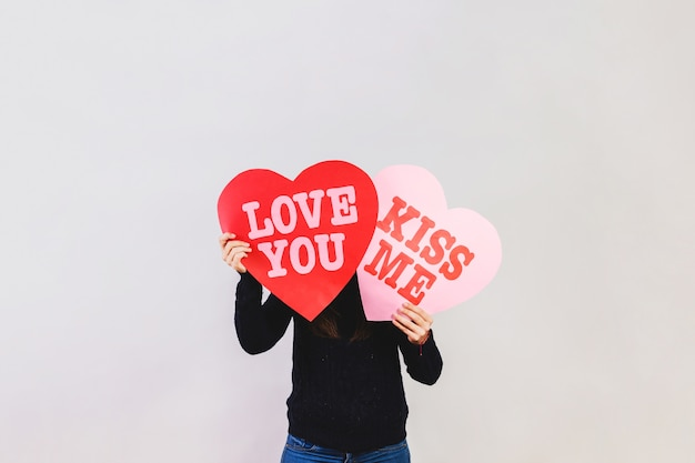 Man holding hearts with messages of love Free Photo