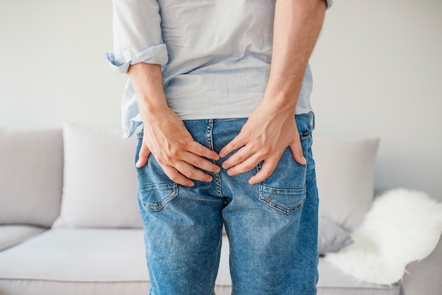 Man holding his bottom in pain, isolated in grey Premium Photo