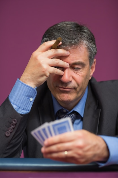 Man holding his cards thinking Premium Photo