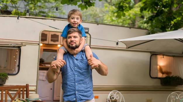 Мужчина держит сына на плечах рядом с караваном с копией пространства Бесплатные Фотографии