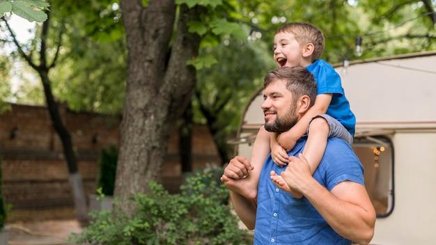 Мужчина держит сына на плечах с копией пространства Бесплатные Фотографии