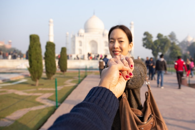 Man holding his wife hand showing wedding ring with taj mahal in background. Premium Photo