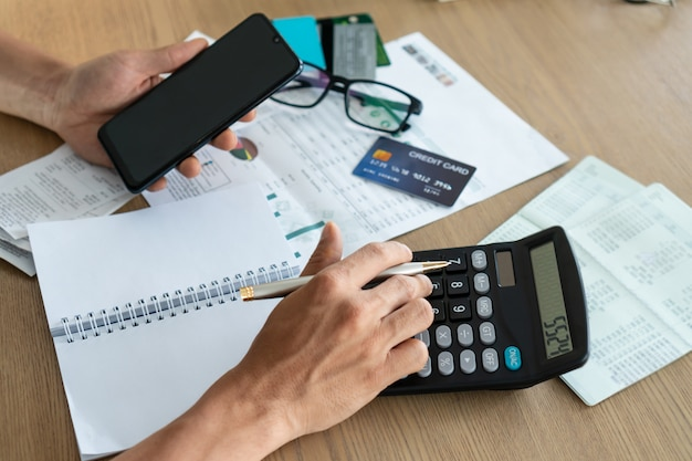 Man holding mobile phone and using calcutor, account and saving concept Premium Photo
