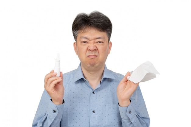 A man holding a nasal spray in his hand on white. Premium Photo