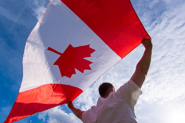 Man holding the national flag of canada against blue sky Premium Photo
