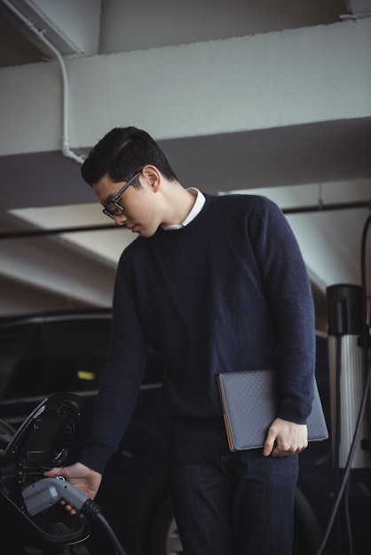 Uomo con organizzatore durante la ricarica di auto elettriche Foto Gratuite